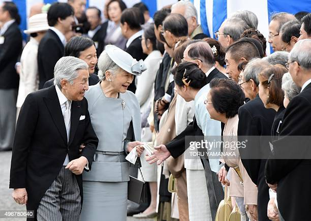 Japanese Emperor Akihito and Empress Michiko greet guests during the annual autumn garden party at the Akasaka Palace imperial garden in Tokyo on...
