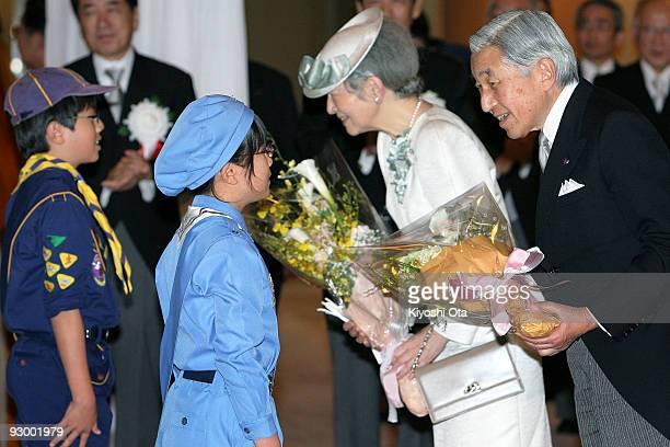 Japanese Emperor Akihito and Empress Michiko receive flower bouquets from Girl Scout Kurumi Sasaki and Boy Scout Ryotaro Nishimiya upon their...