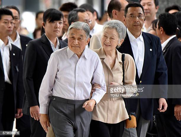 Japanese Emperor Akihito and Empress Michiko smile at people seeing them off before departing Tokyo Station for the Imperial Villa in Nasu to spend...