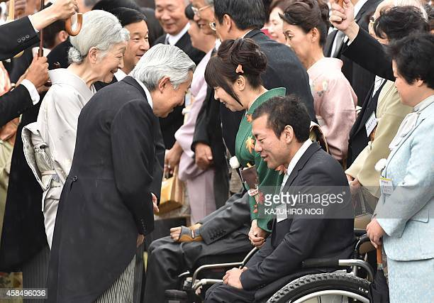 Japanese Emperor Akihito and Empress Michiko speak to Akira Kano an alpine skier and gold medalist in the 2014 Winter Paralympics in Sochi as the...