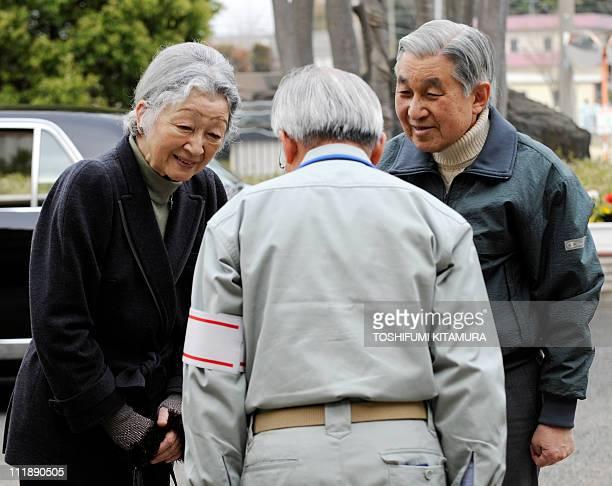 Japanese Emperor Akihito and Empress Michiko speak with Futaba town mayor Katsutaka Idogawa while visiting the Futaba town residents' makeshift...