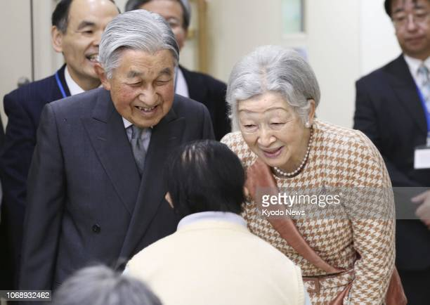 Japanese Emperor Akihito and Empress Michiko talk with a resident of a welfare facility set up for people with learning disabilities in Tokyo's...
