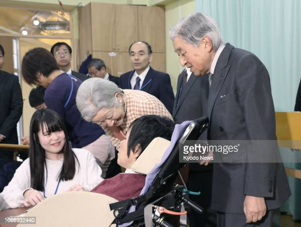 Japanese Emperor Akihito and Empress Michiko talk with people with learning disabilities during their visit to a welfare facility in Tokyo on Dec 6...
