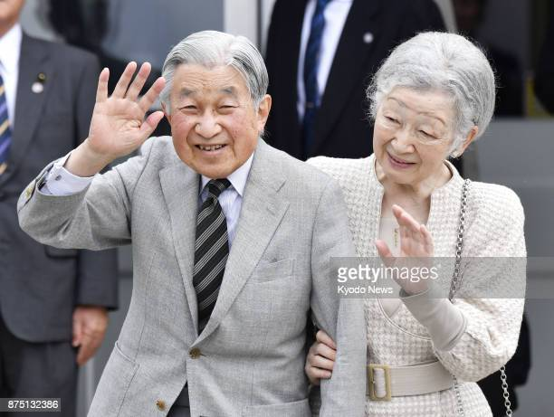 Japanese Emperor Akihito and Empress Michiko wave to local residents after arriving at Yoron Island southwestern Japan on Nov 17 during their...