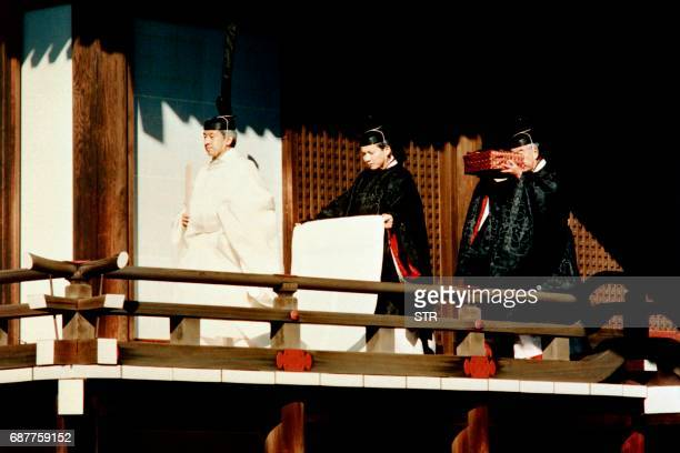 Japanese Emperor Akihito is assisted by an official of the Imperial Household Agency as he walks to a Shinto sanctuary inside the Imperial Palace to...