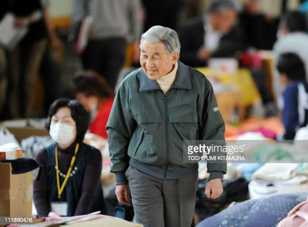Japanese Emperor Akihito leans in to speak with an evacuee from Futaba in Fukushima prefecture at their makeshift shelter in Kazo Saitama prefecture...