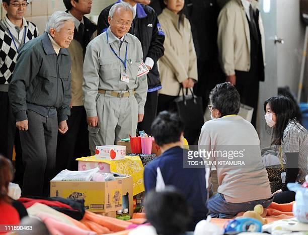 Japanese Emperor Akihito speaks next to Futaba town mayor Katsutaka Idogawa with evacuees from Futaba in Fukushima prefecture at their makeshift...