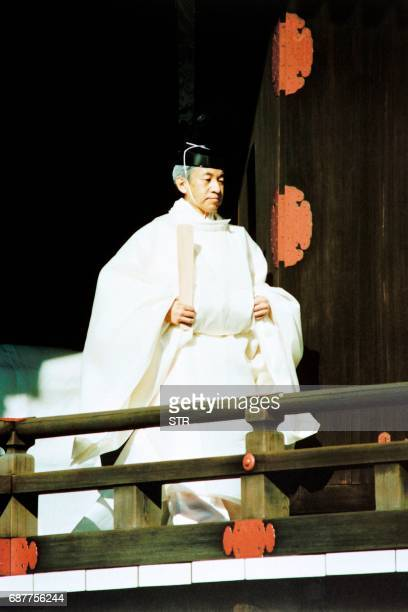 Japanese Emperor Akihito walks to a Shinto sanctuary inside the Imperial Palace for an early morning private ceremony on November 12 1990 to pray and...
