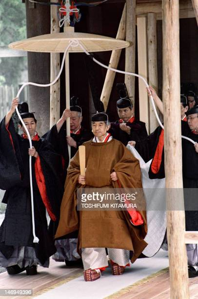Japanese Emperor Akihito walks toward a carriage after he reported his enthronement to the diety of the outer shrine at Ise November 27 during the...
