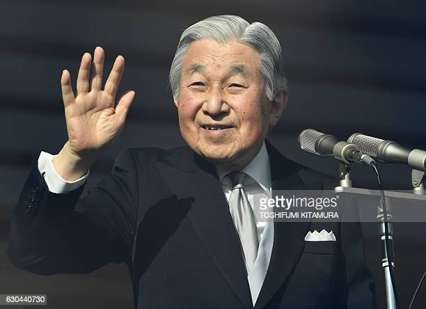 Japanese Emperor Akihito waves to wellwishers as he makes a public appearance on the balcony of the Imperial Palace in Tokyo on December 23 2016...