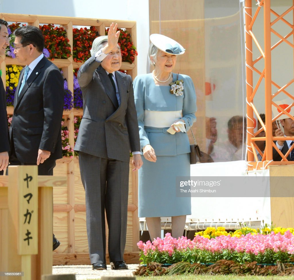 Japanese Emperor Akihito (L) with Empress Michiko waves to the crowd as they arrive at the annual national tree planting festival at Tottori Hanakairo Flower Park on May 26, 2013 in Nanbu, Tottori, Japan.
