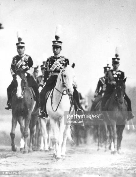 Japanese Emperor Hirohito , in full ceremonial attire, rides a white horse at the head of a column of similarly uniformed men, May 1932.