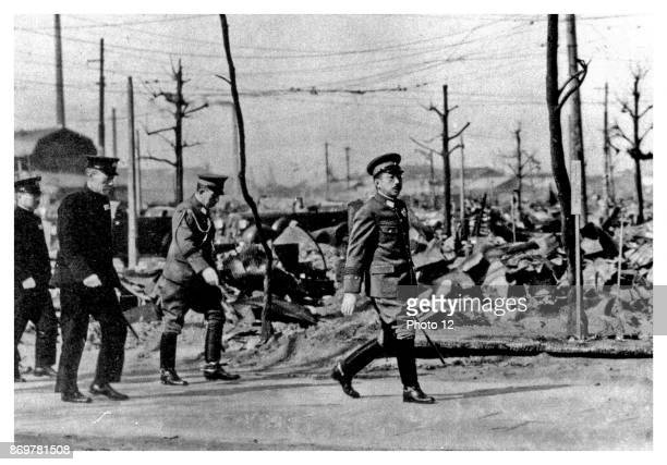 Japanese Emperor Hirohito walks through the ruins of Tokyo following US air Force bombing in the later months of World war two