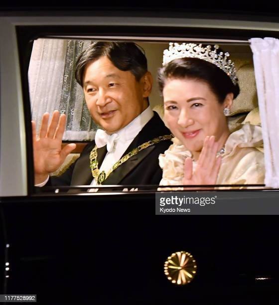 Japanese Emperor Naruhito and Empress Masako are driven to the Imperial Palace in Tokyo on Oct. 22 following his enthronement ceremony earlier in the...