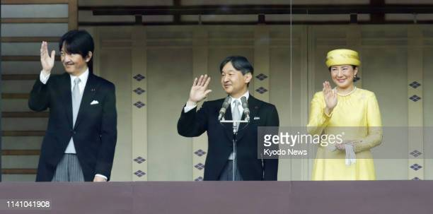 Japanese Emperor Naruhito Empress Masako and his younger brother Crown Prince Fumihito wave to thousands of wellwishers gathered at the Imperial...