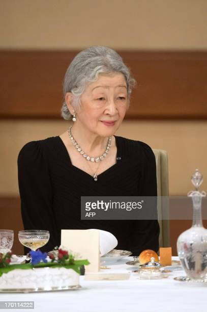 Japanese Empress Michiko listens on June 7 2013 to her husband the Emperor Akihito delivering a speech during a state dinner for the French President...