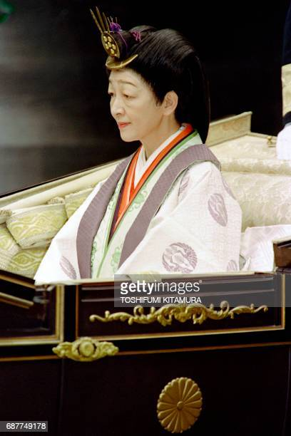 Japanese Empress Michiko sits in a carriage after Emperor Akihito reported his enthronement to the diety of the outer shrine at Ise on November 27...