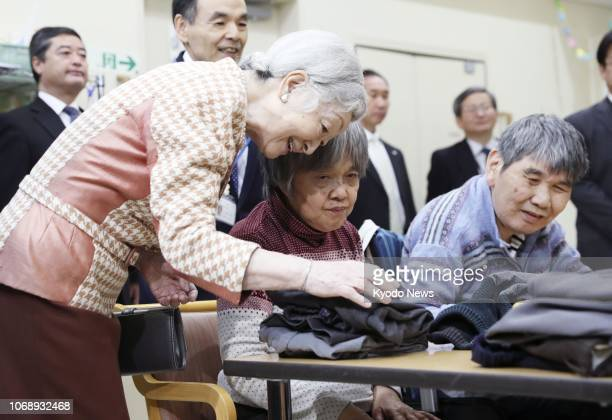 Japanese Empress Michiko talks with people with learning disabilities during her visit to a welfare facility along with Emperor Akihito in Tokyo on...