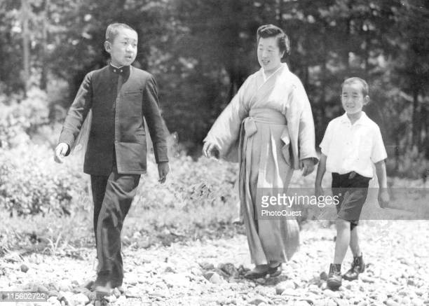 Japanese Empress Nagako walks on the grounds of the Gakushuin Peers' School with her sons Crown Prince Akihito and Prince Yashi Tokyo Japan July 29...