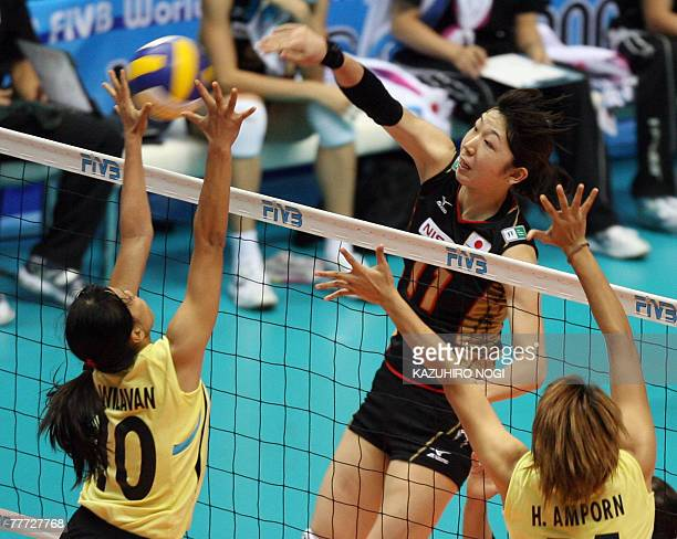 Japanese Erika Erika Araki spikes the ball over Thailand's blockers, Wilavan Apinyapong and Ampron Hyapha during their second round match of the...