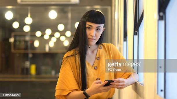 japanse etniciteit vrouw portret met behulp van mobiel op het werk studio - mobile stockfoto's en -beelden
