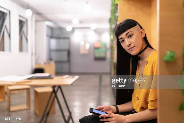japanese ethnicity woman using mobile at startup modern office - punk person stock pictures, royalty-free photos & images