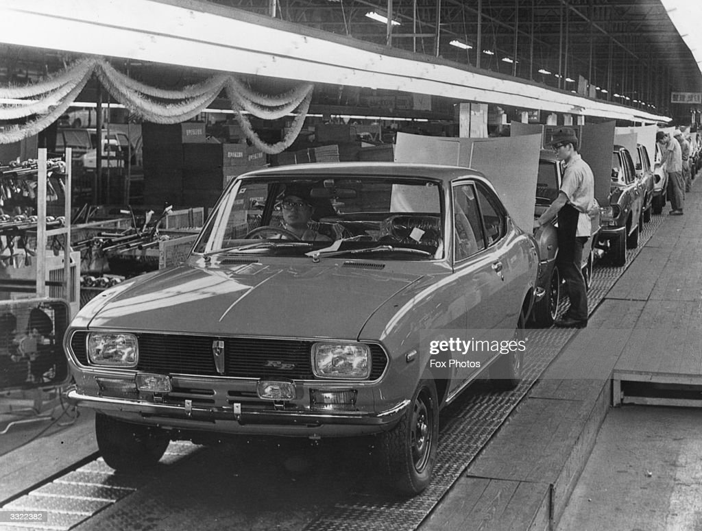 Japanese factory workers assembling cars on a production ...
