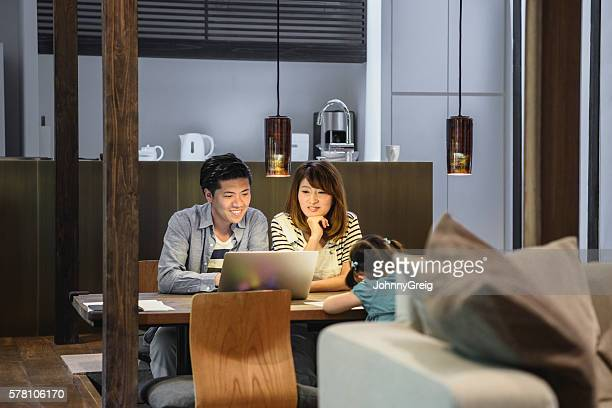 Japanese family at home, parents watching laptop