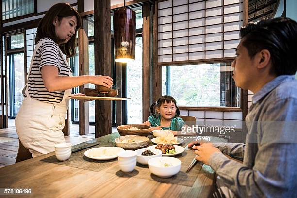 Japanese family eating dinner, mother serving food