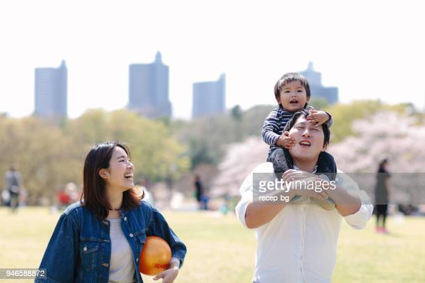japanese family having fun in spring - carrying a person on shoulders stock photos and pictures