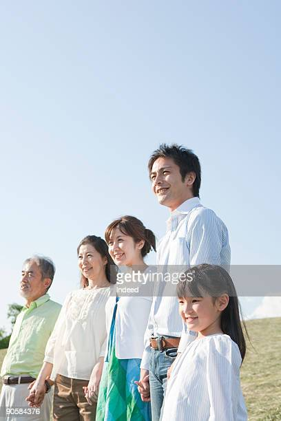 Japanese family holding hands, looking away