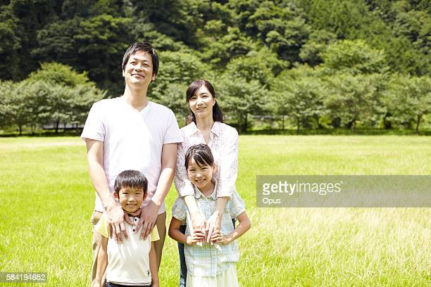 Japanese Family Standing in a Park and Hugging