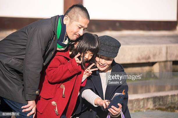 Japanese family taking pictures in temple, Kyoto