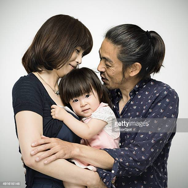 Japanese family with parents embracing the baby daughter