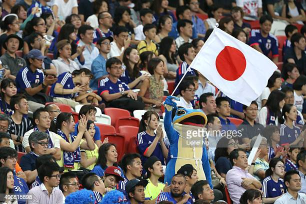 Japanese fan dressed as a mascot waves the Japanese flag after the 2018 FIFA World Cup Qualifier match between Singapore and Japan at National...