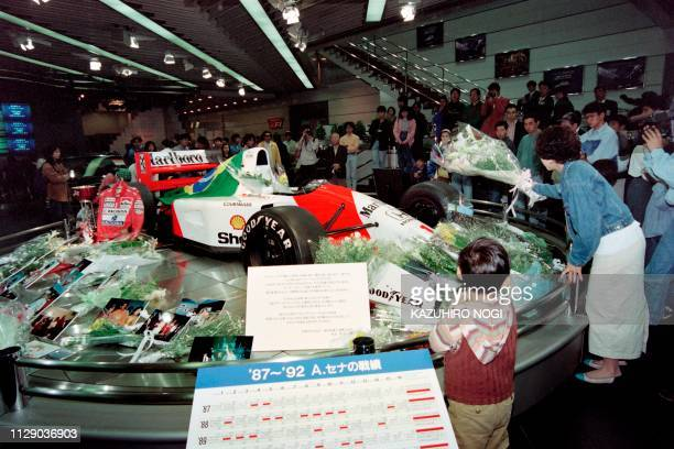 A Japanese fan tosses a bouquet onto the Honda MP4/7 which was driven in 1992 by Brazil's threetime Formulaone champion Ayrton Senna at a Honda's...