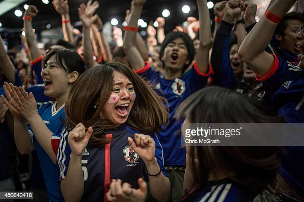 Japanese fans celebrate a goal as they watch the 2014 FIFA World Cup match between Ivory Coast and Japan on a big screen in Shibuya District on June...