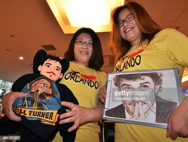 Japanese fans display a handmade stuffed doll and a sketch of British actor Orlando Bloom as they greet the movie star upon his arrival at the Haneda...