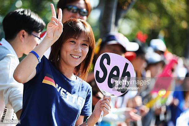 Japanese fans of Sebastian Vettel of Germany and Infiniti Red Bull Racing wait for him to arrive at the circuit before the Japanese Formula One Grand...