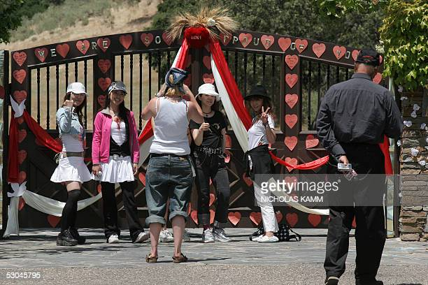 Japanese fans pose for a picture 09 June 2005 in front of US pop star Michael Jackson's Neverland ranch in Los Olivos, 50km south of Santa Maria...