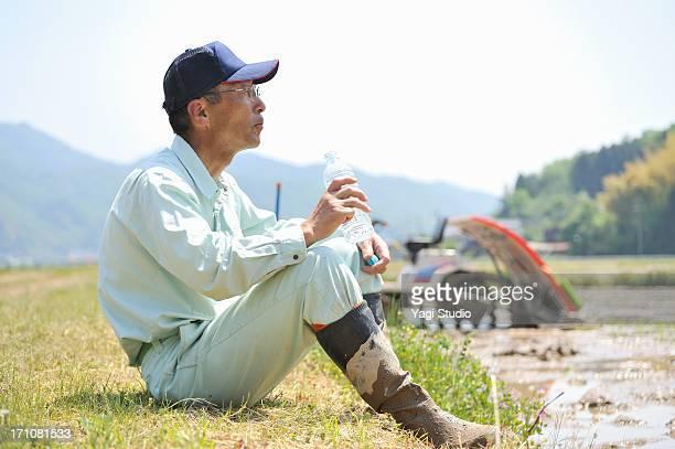 Japanese farmer drinking water and taking a break