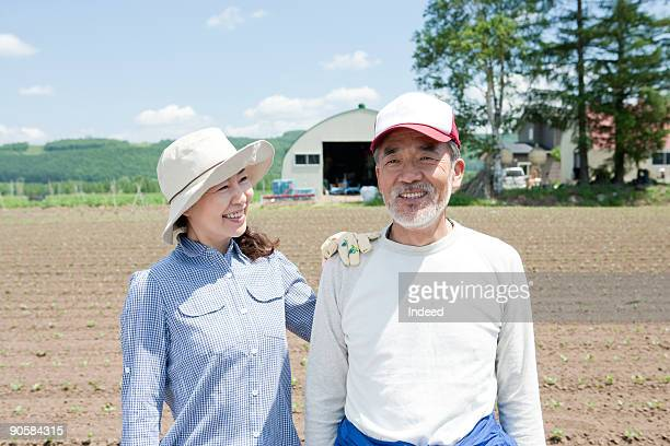 Japanese farming couple smiling on field