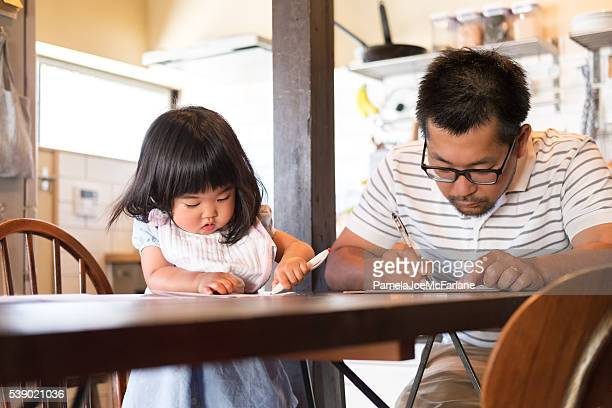 japanese father and daughter filling out paperwork on kitchen table - form filling stock pictures, royalty-free photos & images