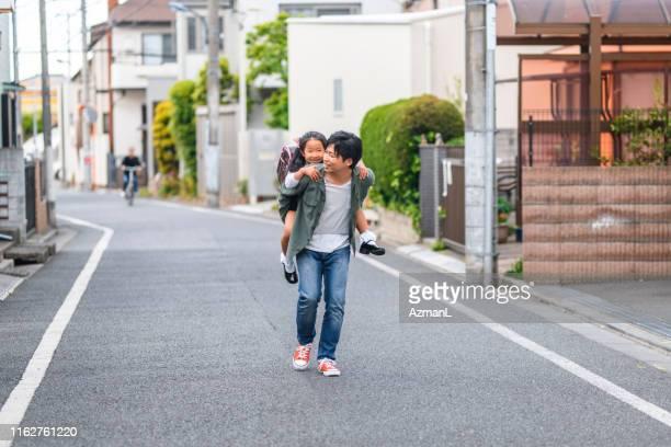 japanischer vater und tochter piggybacking home von der schule - genderblend stock-fotos und bilder