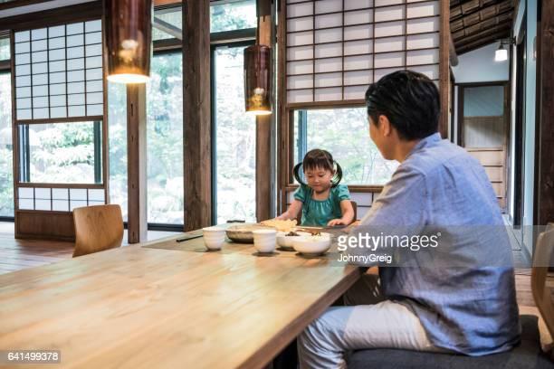 日本人の父親と自宅で食事を食べて座っている娘