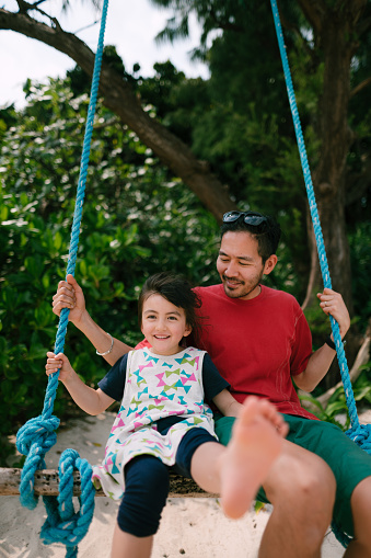 Japanese father and his mixed race daughter on swing, Japan - gettyimageskorea