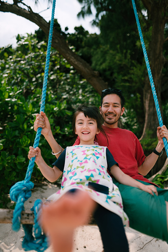 Japanese father and his mixed race preschool girl having fun on swing, Japan - gettyimageskorea