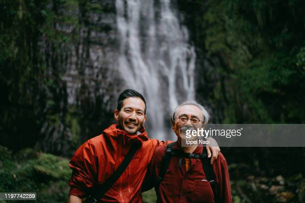 japanese father and son smiling at camera in nature - disruptaging stock pictures, royalty-free photos & images