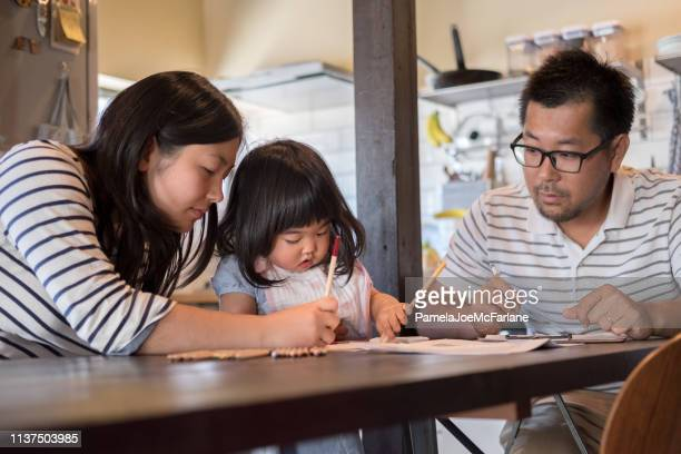 japanese father completing paperwork looks at daughter learning to draw - uomini di età media foto e immagini stock