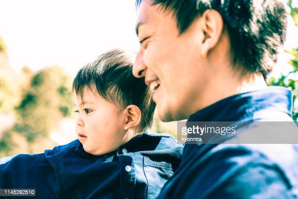 Japanese father is holding his son